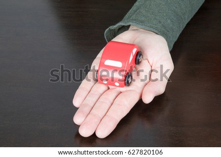 red toy car over palm of hand of man with green shirt on dark brown wooden table