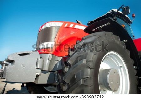 Red tractor against the clear blue sky close-up - stock photo