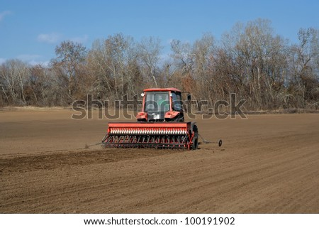 red tractor and seeding attachment on the field - stock photo