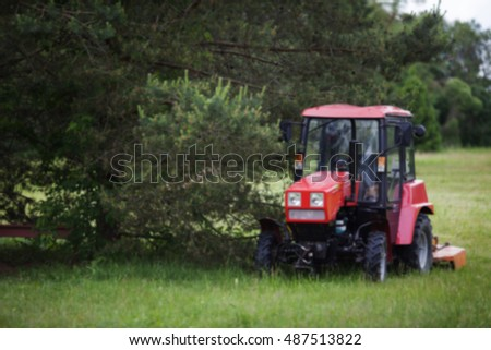 red tractor by the green tree in summer Park