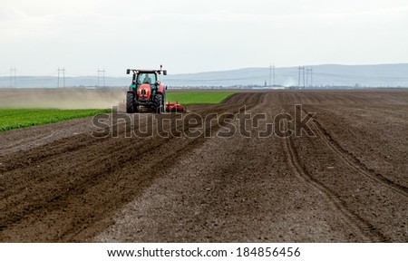 Red tractor cultivating field - stock photo