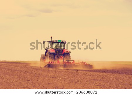 Red tractor driven by farmer cultivating land at spring, filtered image to achieve old cross processing xpro look - stock photo