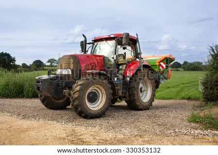 Red tractor on countryside farm field