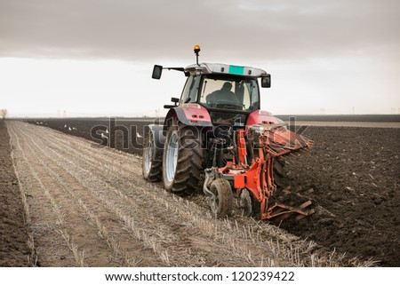 Red Tractor Plowing in Autumn - stock photo