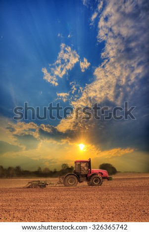 Red tractor plowing the field on sunset