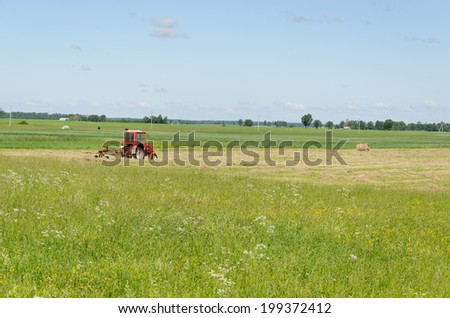 Red tractor ted hay drying grass in agriculture field. Preparing feed for animals.  - stock photo