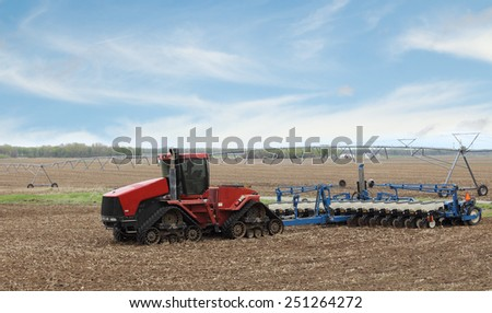 Red tractor with seeder in a farm field - stock photo