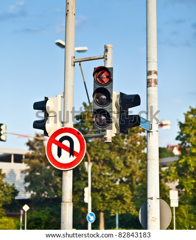 Red traffic light and do-not-turn sign - stock photo