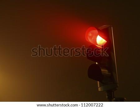 Red traffic light in fog - stock photo