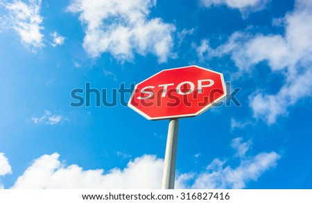 Red traffic stop sign against the blue sky
