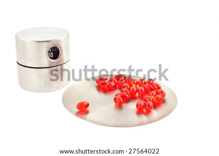 red transparent vitamin pills on a steel round plate and steel timer. white background - stock photo