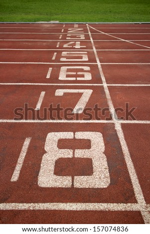 Red treadmill at the stadium with the numbering from one to eight