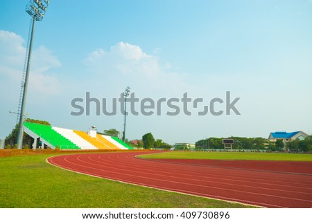 Red treadmill, Red running track at the stadium with green grass on blue sky - stock photo