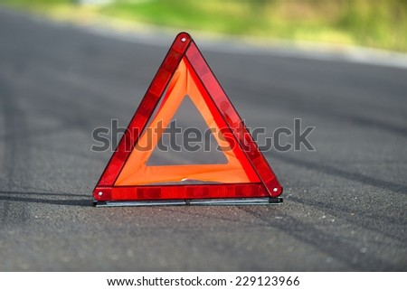 Red triangle of a car on the road - stock photo