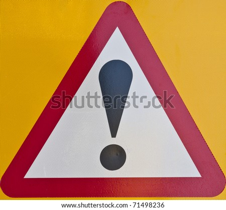 Red triangle warning sign with an exclamation mark - stock photo