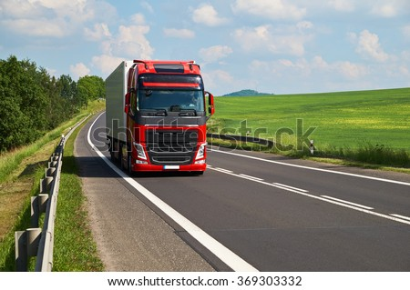 Red truck driving on asphalt road in a rural landscape. Green fields and alleys leading along the road. Sunny summer day with a cloudy sky.