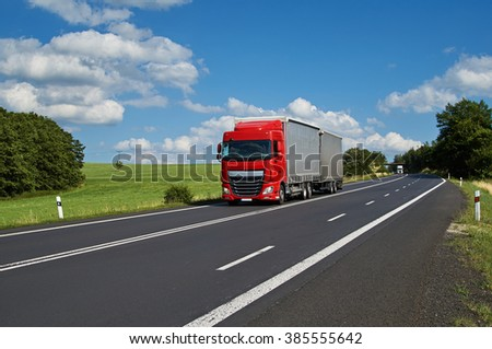 Red truck driving on asphalt road in a rural landscape. White truck coming from afar. Sunny summer day with blue skies and white clouds. - stock photo
