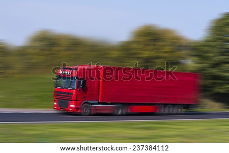 Red Truck on a fast express road, motion blur - stock photo