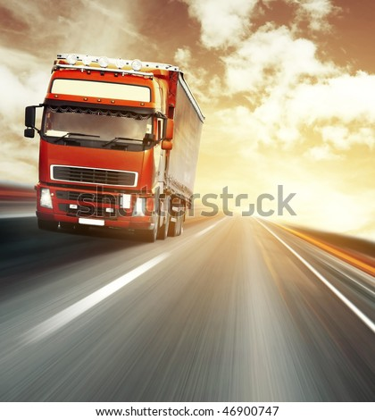 Red truck on blurry asphalt road under red sky with clouds and sunset light - stock photo