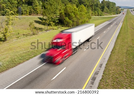 Red Truck Speeding Down The Highway/ Blurred Motion/ Scenic Horizontal Color Image  - stock photo