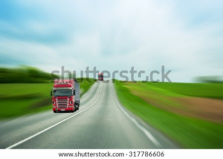 Red trucks on blurry highway and green field driving for fast delivery of goods, parcels and industries - stock photo