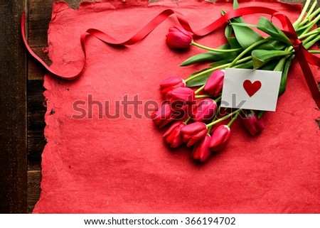Red tulip bouquet with red heart message card on the red paper