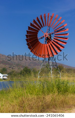 Red turbines for pump water and lagoon - stock photo