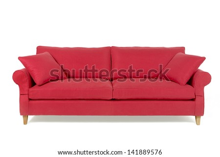Red two-seat sofa with pillows, isolated on white.