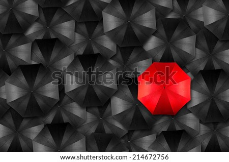 red umbrella in middle of black umbrellas - stock photo