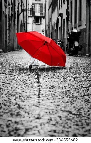 Red umbrella on cobblestone street in the old town. Wind, rain, stormy weather. Color in black and white conceptual, idea. Vintage, retro style. - stock photo