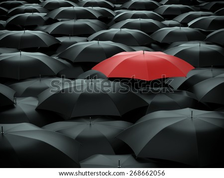 Red umbrella over many black umbrellas - stock photo