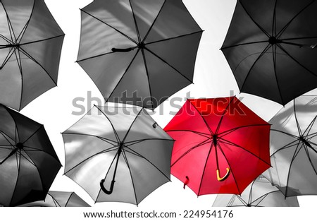 red umbrella standing out from the crowd - stock photo