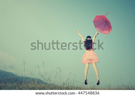 Red umbrella woman jump to sky.Summer Vacation concept.Vintage Tone. - stock photo
