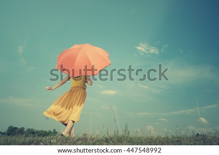 Red umbrella woman standing and cloud sky.Summer Vacation concept.Vintage Tone. - stock photo