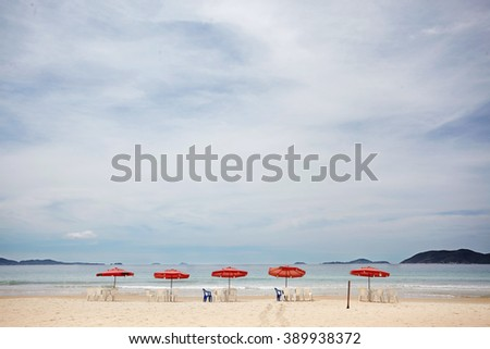 Red umbrellas on a tropical beach - stock photo
