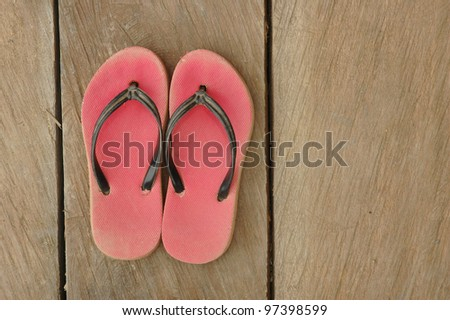 red used flip-flops on wooden board - stock photo