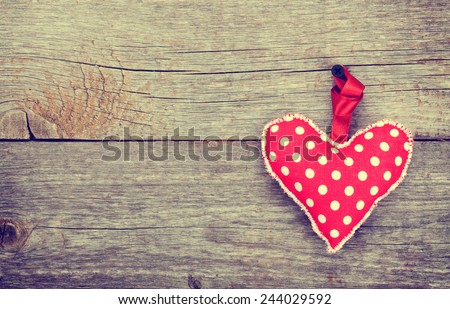 Red Valentine's day heart toy. On wooden background with copy space. Toned - stock photo