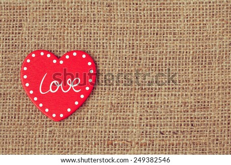 Red valentine's day holiday heart on retro textile background with vintage instagram toning - stock photo