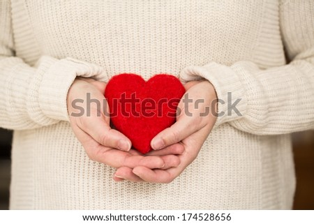 Red Valentines Day heart resting in woman's hands
