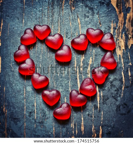 Red Valentines Day heart shaped candy border on dark texture wooden background - stock photo