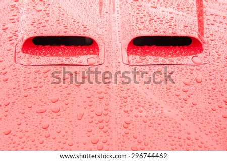 red vehicle panels covered in raindrops - stock photo