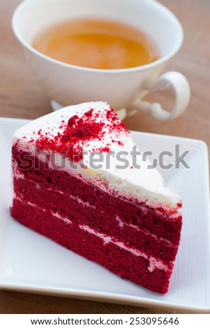 Red velvet cake closeup with cup of tea on wooden board - stock photo