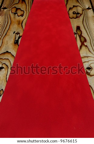 Red velvet carpet fabric over a wooden floor - stock photo