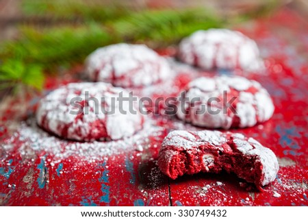 Red velvet crinkle cookies cooling on a vintage red wooden table for Christmas holiday baking - stock photo