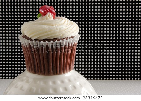 Red velvet cupcake with butter cream frosting against a yellow background. - stock photo