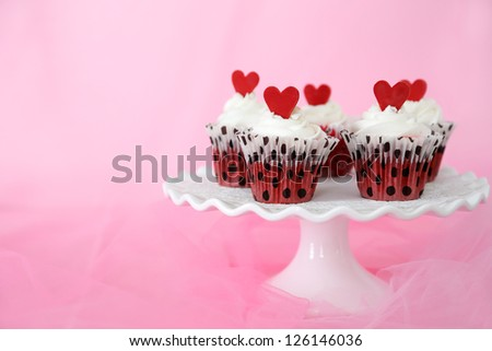 Red velvet cupcakes with cream cheese frosting decorated with red chocolate hearts. Copy space on the side. - stock photo