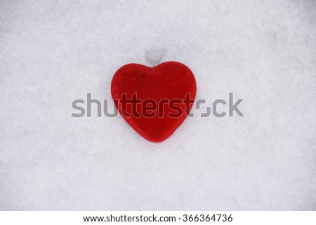 red velvet fabric heart on snow background, heart is symbols of love