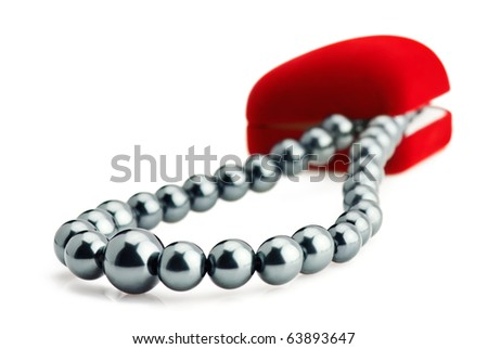 Red velvet gift box and black pearl necklace over white - stock photo