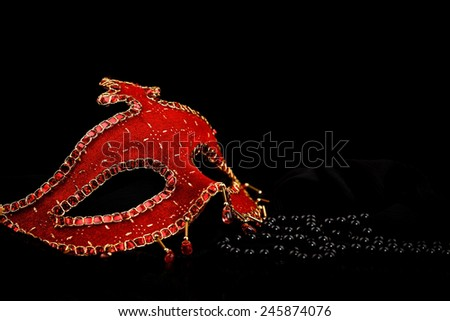Red Venice mask and black pearls with reflection over black background - stock photo