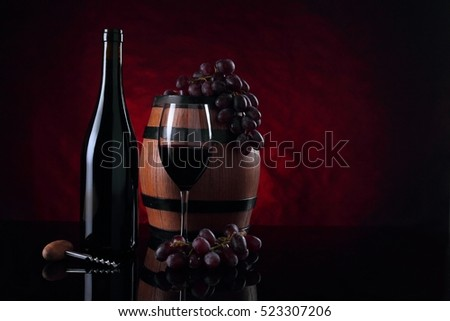 Red vine bottle, old wooden barrel and grapes